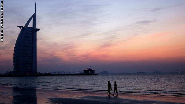 A couple strolls along Jumeirah beach ne