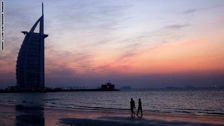 A couple strolls along Jumeirah beach ne
